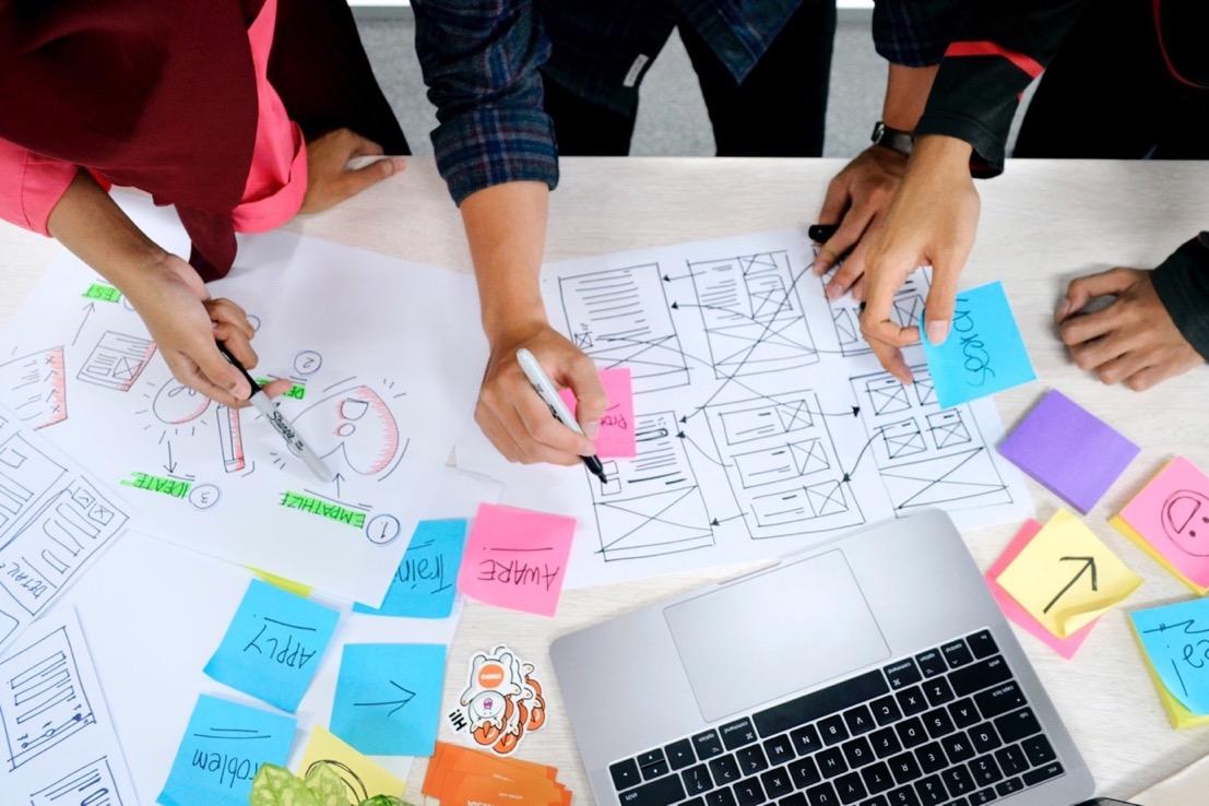 一群設計師拿著wireframe討論